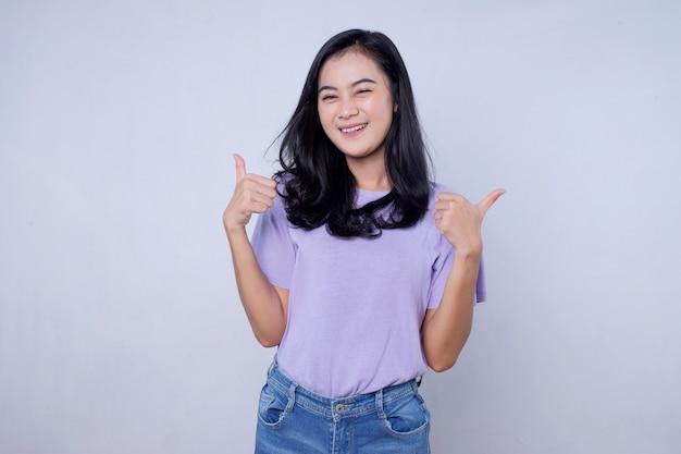 Gelukkig lachend prachtige vrouw die duim omhoog laat zien, leuk vinden om geweldig idee goed te keuren op een lichte witte muur