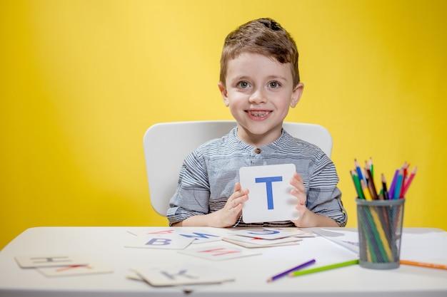 Gelukkig lachend preschool jongetje toont brieven thuis huiswerk maken