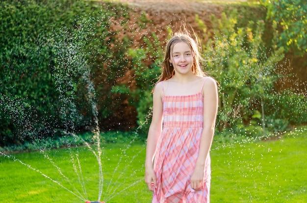 Gelukkig lachend preteen meisje in de zomertuin nat van waterdruppels spray van water pijp