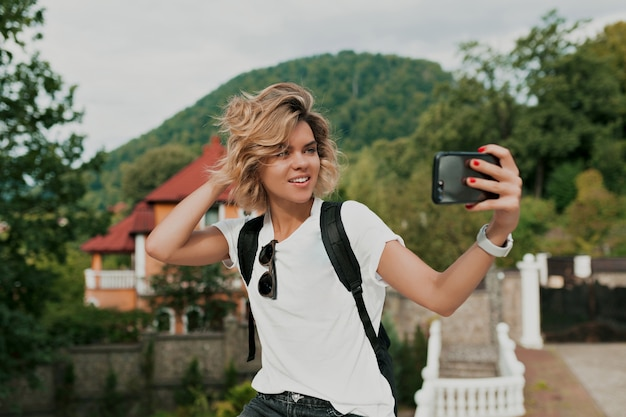 Gelukkig lachend reiziger meisje met krullend kapsel selfie maken over berg. reiziger die in vrouwelijke handmobiel gebruikt. toeristische blik op berg, zomerlevensstijl