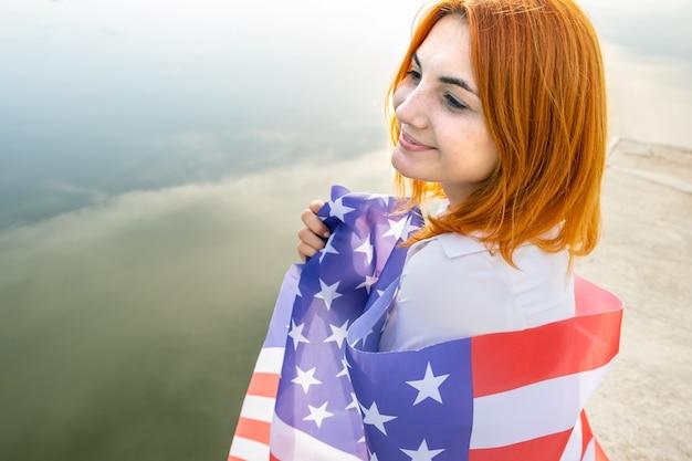 Gelukkig lachend roodharig meisje met de nationale vlag van de vs op haar schouders. positieve jonge vrouw die de onafhankelijkheidsdag van de verenigde staten viert.