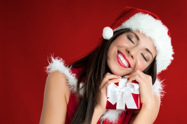 Gelukkig lachend santa meisje met een ingepakt cadeau voor kerstmis
