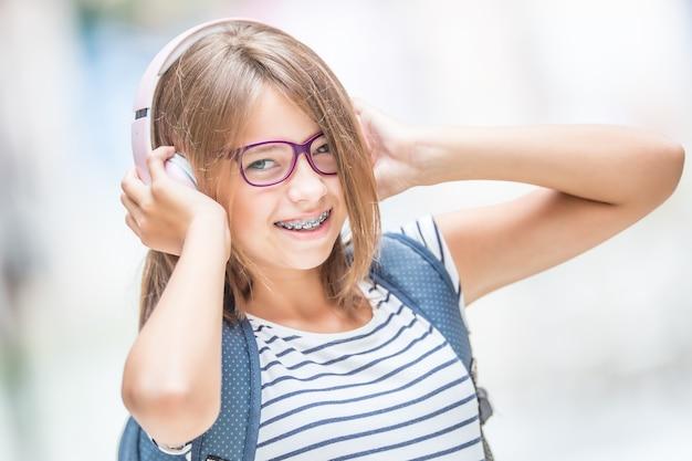 Gelukkig lachend schoolmeisje met tandheelkundige beugels en bril luisteren muziek van koptelefoon... orthodontist en tandarts concept.