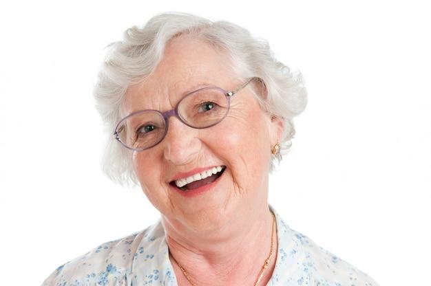 Gelukkig lachend senior dame met haar bril op wit wordt geïsoleerd