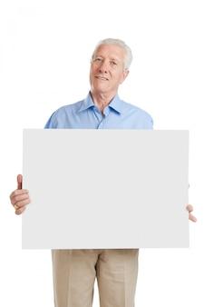Gelukkig lachend senior man met blanco bordje om het te schrijven op uw eigen tekst, geïsoleerd op wit