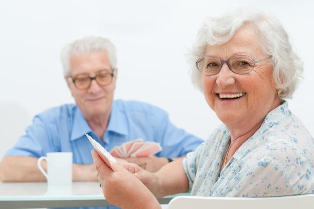 Gelukkig lachend senior paar speelkaarten samen thuis