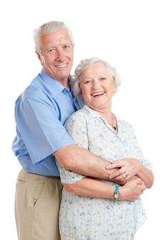 Gelukkig lachend senior paar staande samen met een omhelzing op wit wordt geïsoleerd