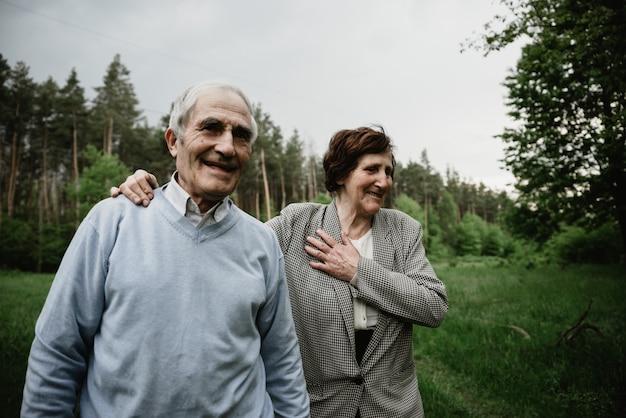 Gelukkig lachend senior paar verliefd op de natuur, plezier maken. bejaarde echtpaar op het groene veld. leuke senior paar wandelen en knuffelen in voorjaar bos