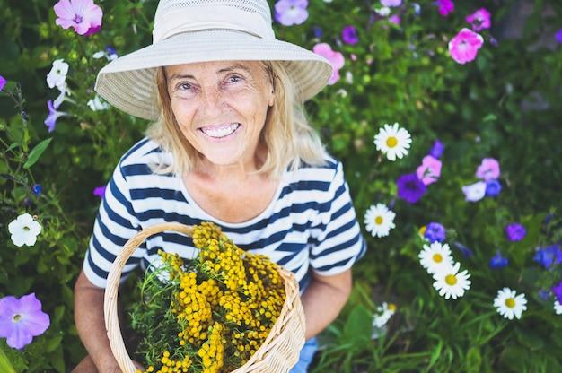 Gelukkig lachend senior vrouw poseren in zomertuin met bloemen in strooien hoed.