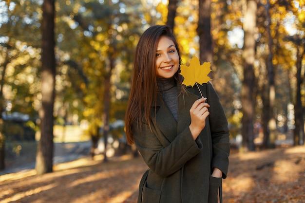 Gelukkig lachend stijlvolle meisje in een modieuze jas met een gouden herfstblad wandelingen in het park op een zonnige dag