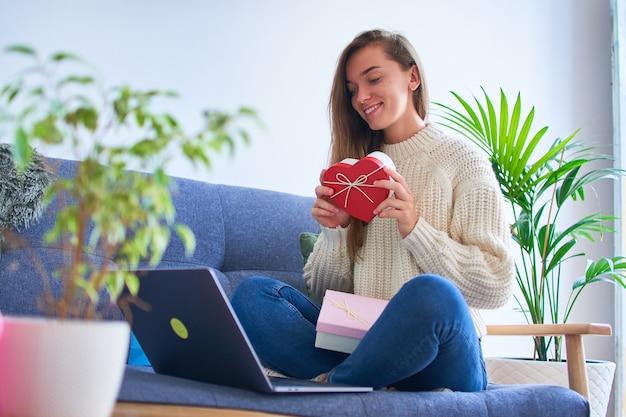 Gelukkig lachend tevreden geliefde vrouw ontving een geschenk online en houdt een hartvormige doos vast voor valentijnsdag 14 februari