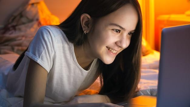 Gelukkig lachend tienermeisje surfen op internet en chatten op laptop 's nachts.