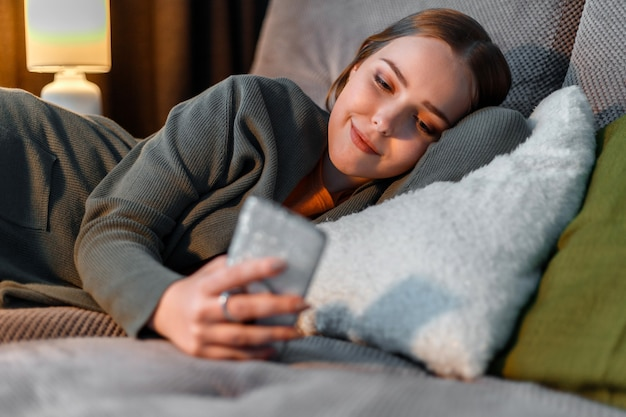 Gelukkig lachend tienermeisje surfen op internet of chatten met behulp van smartphone 's nachts liggend op de bank. jonge vrouw in huiskleren gebruikt smartphone voor het slapengaan voor game- en sociale media-verslaving.