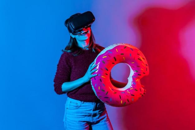 Gelukkig lachend toeristenmeisje in vr-bril met rubberen ring die virtuele reistours bekijkt