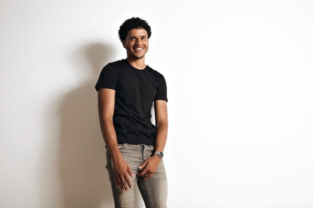 Gelukkig lachend uitnodigende sexy jonge zwarte man in strakke grijze jeans en lege katoenen zwarte t-shirt op wit wordt geïsoleerd