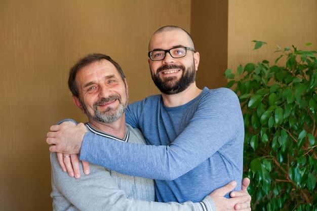 Gelukkig lachend vader en zijn volwassen zoon