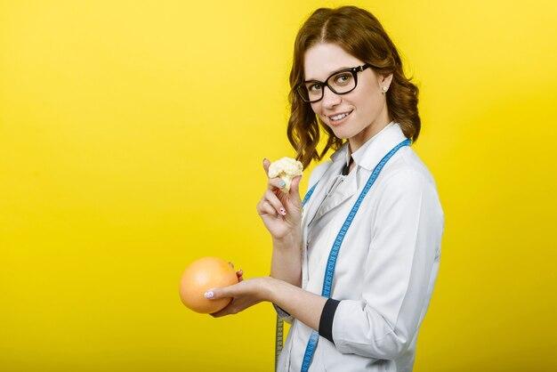 Gelukkig lachend voedingsdeskundige vrouw met grapefruit en broccoli in handen, met een meetlint of meter