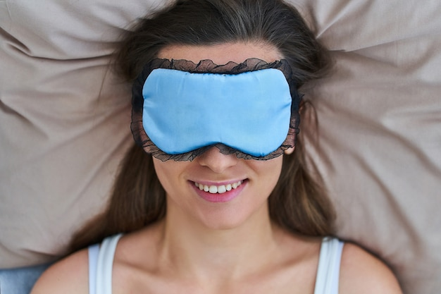 Gelukkig lachend vreugdevolle slapende vrouw met oogmasker voor betere slaap en zoete dromen