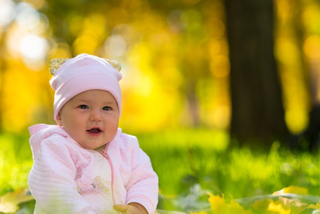 Gelukkig lachend vriendelijke jonge babymeisje zittend op het gras in herfst bos in een close-up portret met kopie ruimte