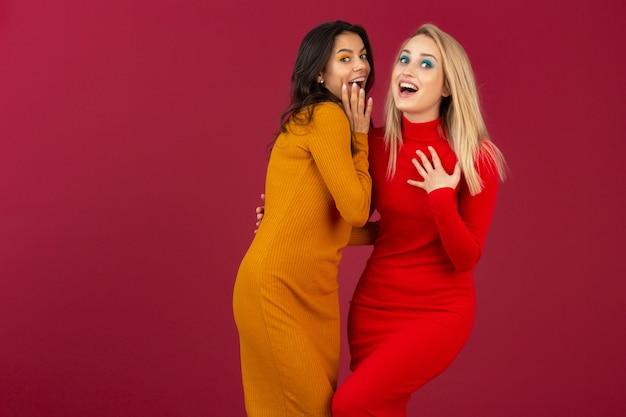 Gelukkig lachend vrij stijlvolle vrouwen in gele en rode herfst winter mode gebreide jurk poseren geïsoleerd op rode muur