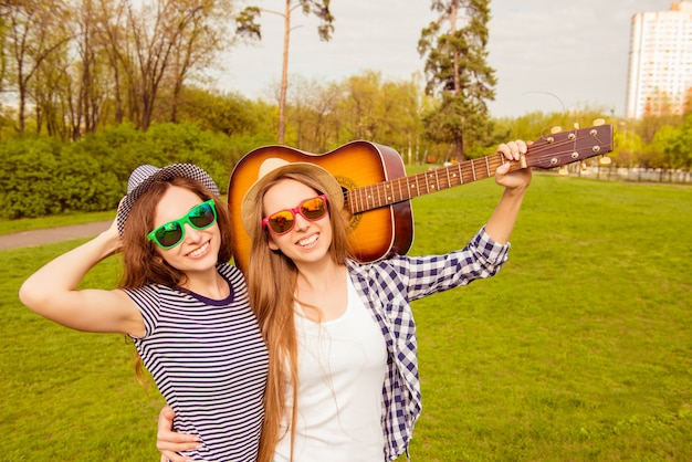 Gelukkig lachend womanfriends in bril wandelen in het park met gitaar