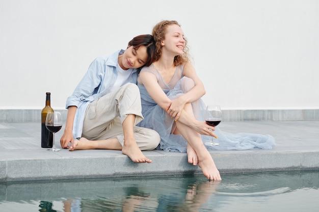 Gelukkig lachend yuong aziatische vrouw leunend op de schouder van vriendin en ogen sluiten met plezier wanneer paar rusten bij zwembad