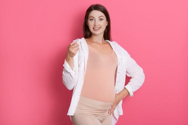 Gelukkig lachend zwangere dame wijzend op camera, ziet er gelukkig uit, raakt haar buik aan, draagt stijlvolle kleding tegen roze muur, donkerharige aanstaande moeder.