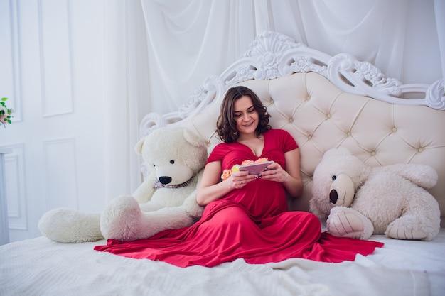 Gelukkig lachend zwangere vrouw zittend op het gras en maakt zelfportret op smartphone. de zwangere vrouw maakt selfie.