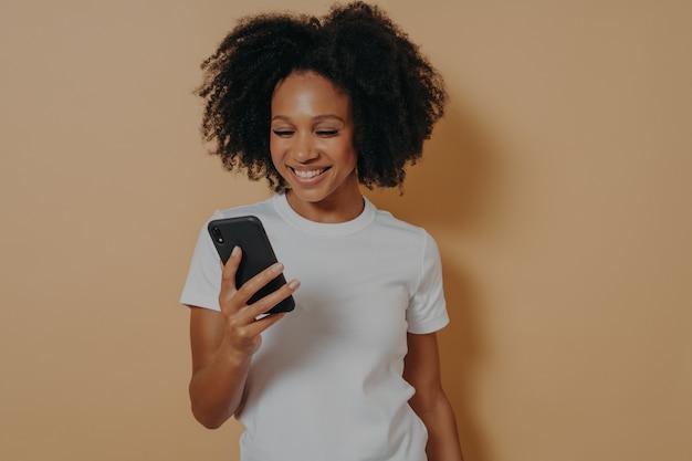 Gelukkig lachende afrikaanse vrouwelijke student met behulp van mobiele telefoon en glimlachen, positief nieuws lezen op internet of online chatten met vriendje, moderne smartphone vasthouden terwijl poseren tegen zand kleur muur