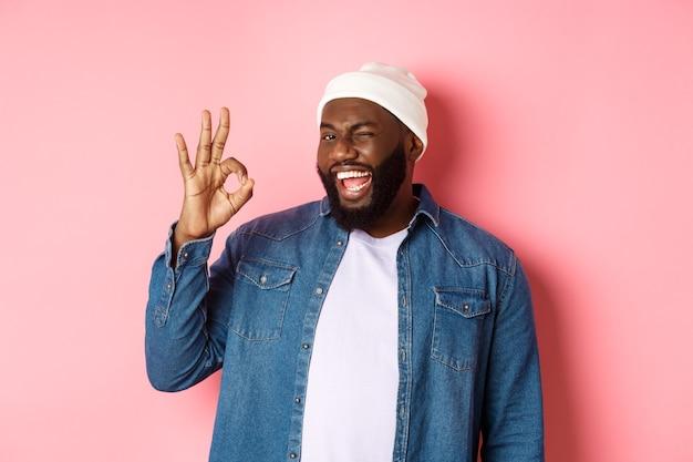 Gelukkig lachende afro-amerikaanse man die goed teken toont, goed aanbod goedkeurt en prijst, staande over roze achtergrond.