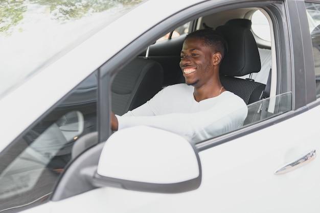 Gelukkig lachende afro-amerikaanse mannelijke bestuurder zit achter het zelfrijdende stuur van een autonome elektrische moderne auto. gelukkige kerel houdt telefoon vast en glimlacht naar camera in moderne elektrische auto Premium Foto