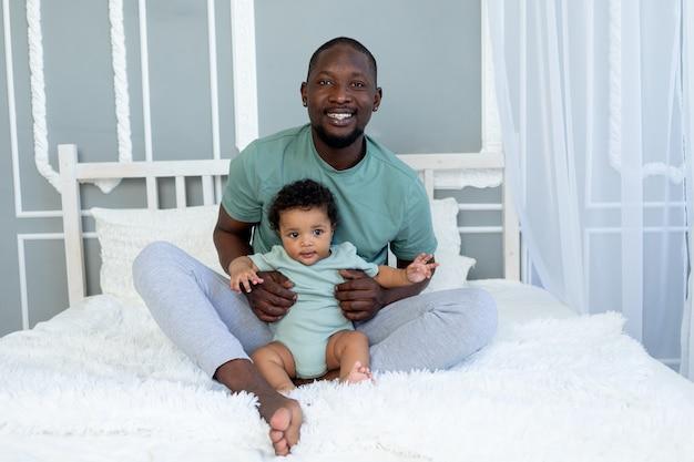 Gelukkig lachende afro-amerikaanse vader met zoontje op bed thuis knuffelen en spelen, gelukkige familie