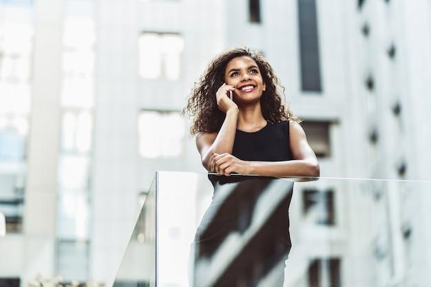 Gelukkig lachende afro-amerikaanse vrouw hebben een leuk gesprek op straat.