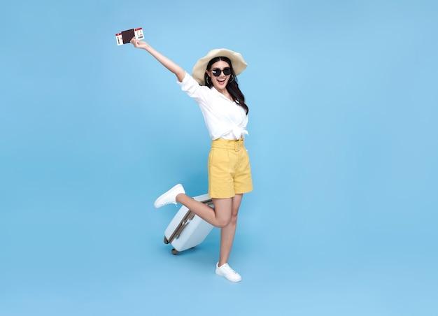 Gelukkig lachende aziatische vrouw gekleed in zomer kleding met paspoort en bagage genieten van hun zomervakantie uitje op blauwe achtergrond.