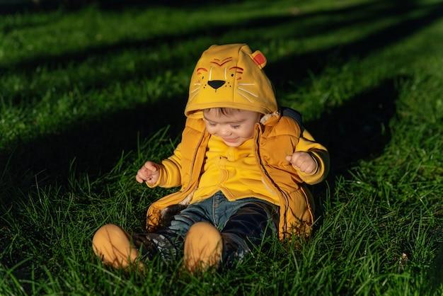 Gelukkig lachende babyjongen in zonsonderganglichten buiten in het herfstpark, het concept van een kindertijdgezin en