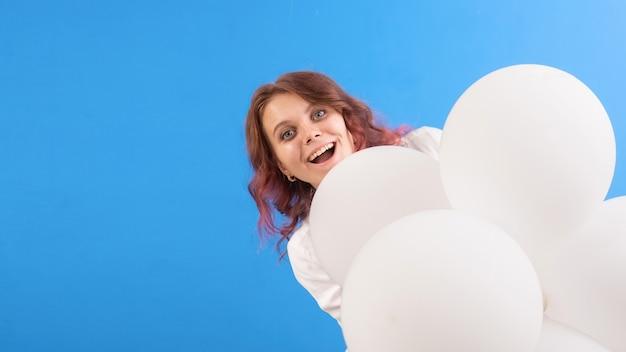 Gelukkig lachende blanke vrouw met witte ballonnen