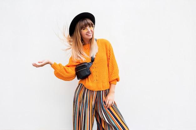 Gelukkig lachende brunette vrouw permanent op wit in stijlvolle oranje trui en veelkleurige streep culotte