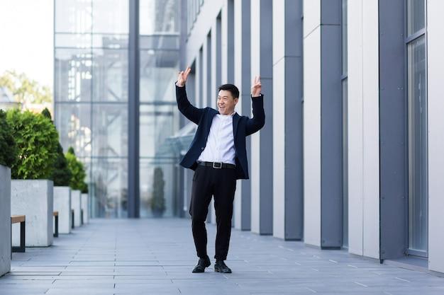 Gelukkig lachende en succesvolle aziatische zakenman danst met plezier en een goed resultaat van zijn werk