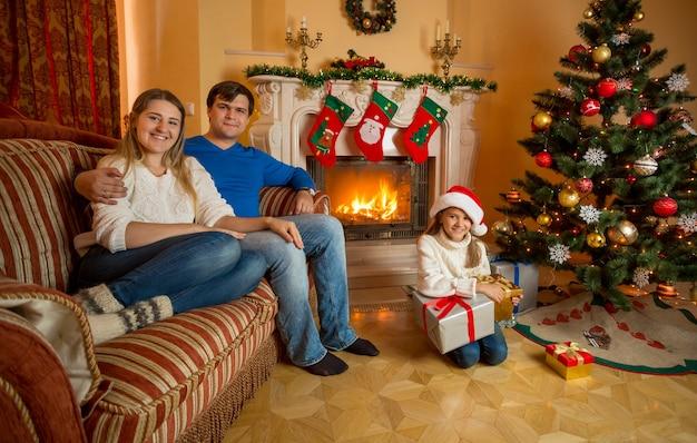 Gelukkig lachende familie poseren in woonkamer ingericht voor kerstmis met brandende open haard