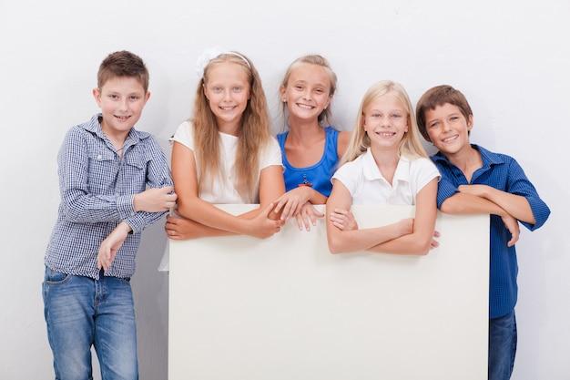 Gelukkig lachende groep kinderen, jongens en meisjes, bord laten zien