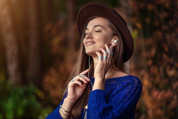 Gelukkig lachende herfst brunette vrouw in een bruine hoed en in een gebreide trui met zilveren ringen met turquoise steen geniet van het luisteren naar herfstmuziek op koptelefoon buitenshuis in de herfst