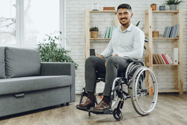 Gelukkig lachende jonge man in een rolstoel thuis