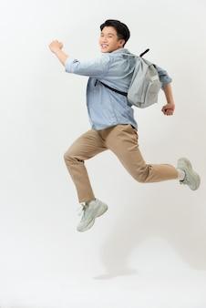 Gelukkig lachende jonge man met rugzak springen in de lucht op witte achtergrond