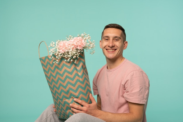 Gelukkig lachende jonge man zittend op de grond, boodschappentas met bloemen te houden