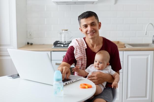Gelukkig lachende jonge volwassen vader met kastanjebruin casual t-shirt zittend aan tafel in de keuken in de buurt van notebook, baby in armen houdend, camera kijkend met positieve uitdrukking.