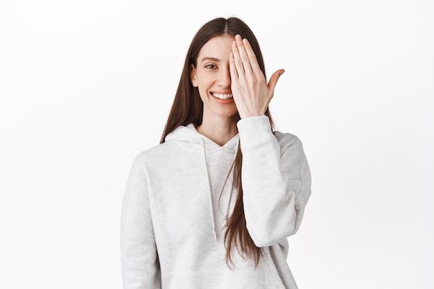 Gelukkig lachende jonge vrouw bedek de helft van het gezicht, kijkend naar de voorkant met één kant, staande in een casual hoodie tegen een witte muur