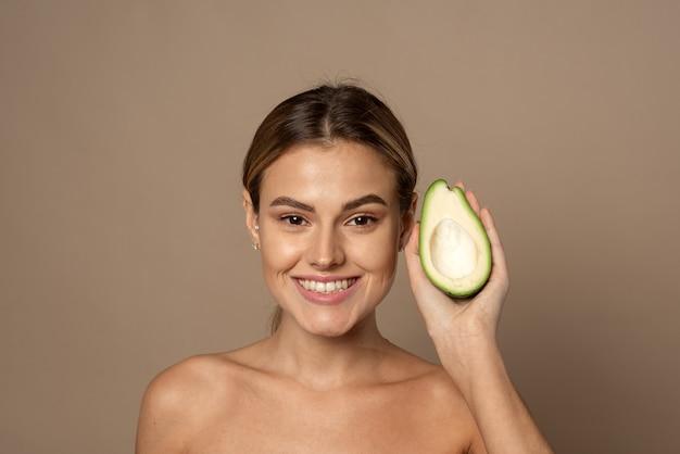Gelukkig lachende jonge vrouw met avocado half op een beige achtergrond. natuurlijk schoonheidsconcept.