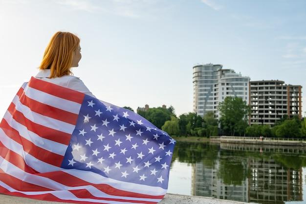 Gelukkig lachende jonge vrouw met de nationale vlag van de vs op haar schouders met hoge stadsgebouwen op de achtergrond die de onafhankelijkheidsdag van de verenigde staten vieren.