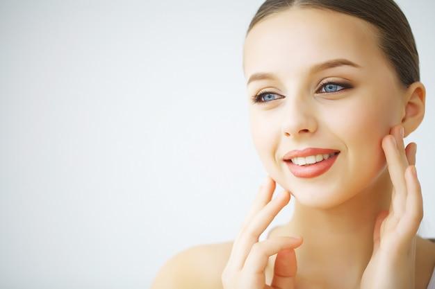 Gelukkig lachende jonge vrouw met perfecte huid, natuurlijke make-up en een mooie glimlach. vrouwelijk portret met blote schouders