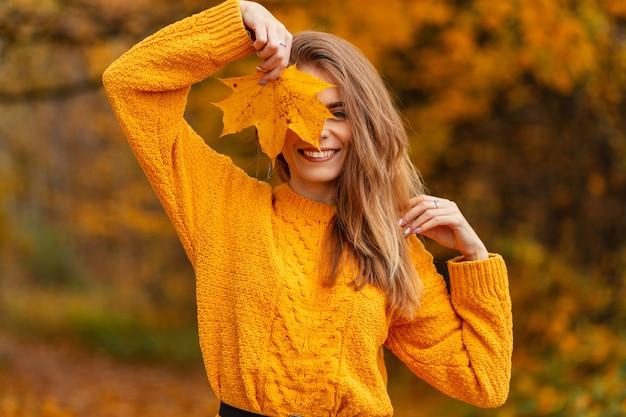 Gelukkig lachende jongedame met schattige glimlach in gele vintage gebreide trui bedekken haar gezicht met gouden herfstblad buiten genieten met gekleurde herfstbladeren. mode vrouwelijke stijl en schoonheid